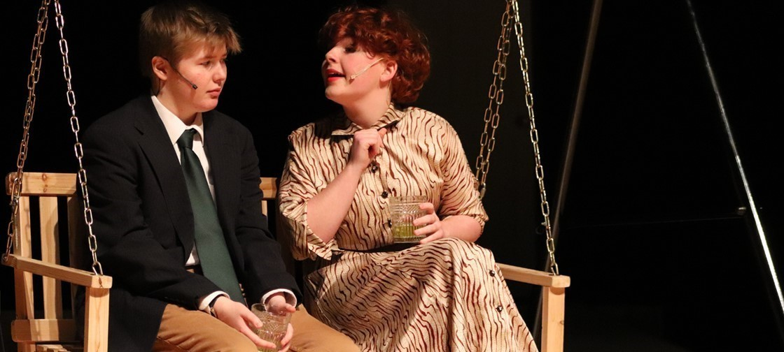 two student actors sitting on a swing