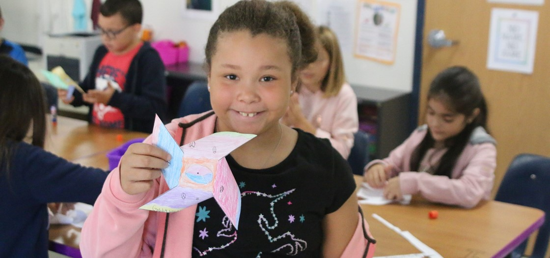 """A Legend student poses with the pinwheel she created for the """"Pinwheels for Peace"""" installation at the school"""