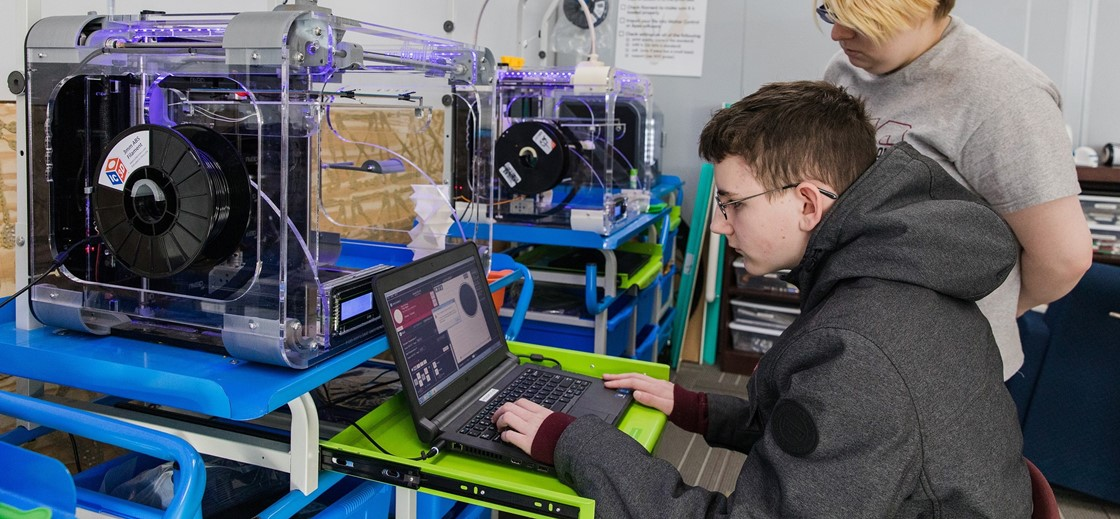 Students work with the 3D printer in the NHS Maker Space