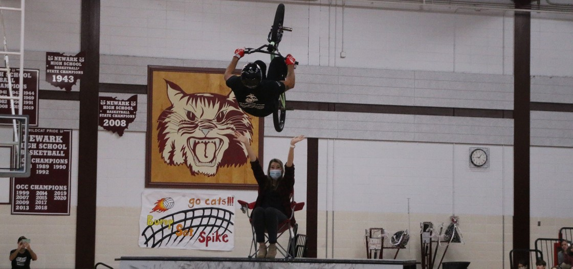 A BMX rider jumps over NHS teacher Miss Brewer during the No Hate Tour visit to the school